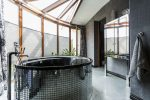 Luxurious bathroom interior with freestanding glossy bathtub, designed in dark tones