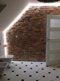 ściana ze starej cegły z podświetleniem w łazience na poddaszu